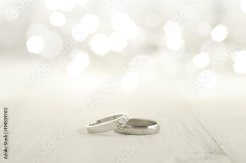 Fotografie, Tablou Two wedding rings place on wooden floor with light bokeh background