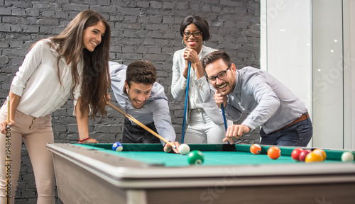 Fotografie, Tablou  Cheerful business people playing billiards during office break.