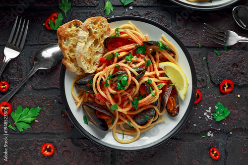 Deurstickers Klaar gerecht Homemade Pasta Spaghetti with mussels, tomato sauce, chilli and parsley on rustic background. sea food meal