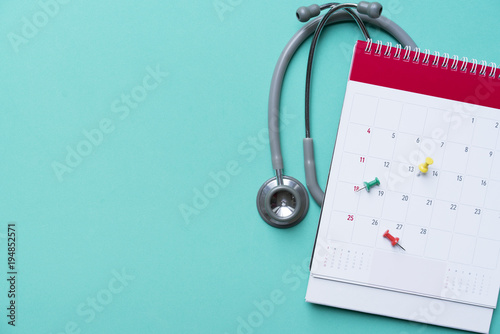 Fotomural  Top view of stethoscope and calendar on the green background, schedule to check