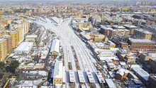 Aerial View Of The Tuscolana Station In Rome, Italy. Around The Tracks There Are The Palaces And Streets Of The Italian City. The Railroad Tracks Are Made Of Steel. Everything Is Covered By Snow.