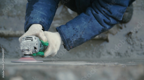 Photo  Builder worker with grinder machine cutting finishing concrete wall at construction site