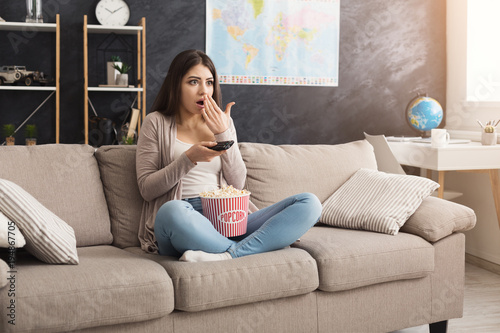 Fotografie, Obraz  Young woman sitting on the couch and watching tv