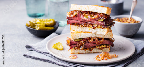 Roast beef sandwich on a plate with pickles.