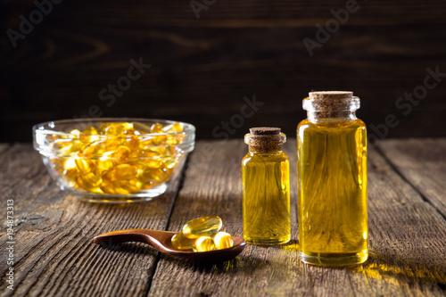 Fototapeta Fish oil capsules on wooden background, vitamin D supplement obraz