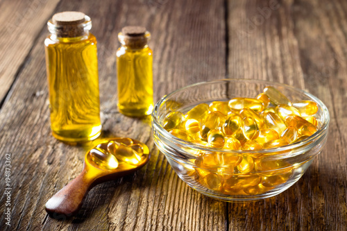 Valokuva  Fish oil capsules on wooden background, vitamin D supplement