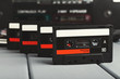 Row of vintage audio cassettes and tape recorder at gray background