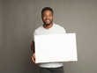 canvas print picture - Picture of young african-american man holding white blank board