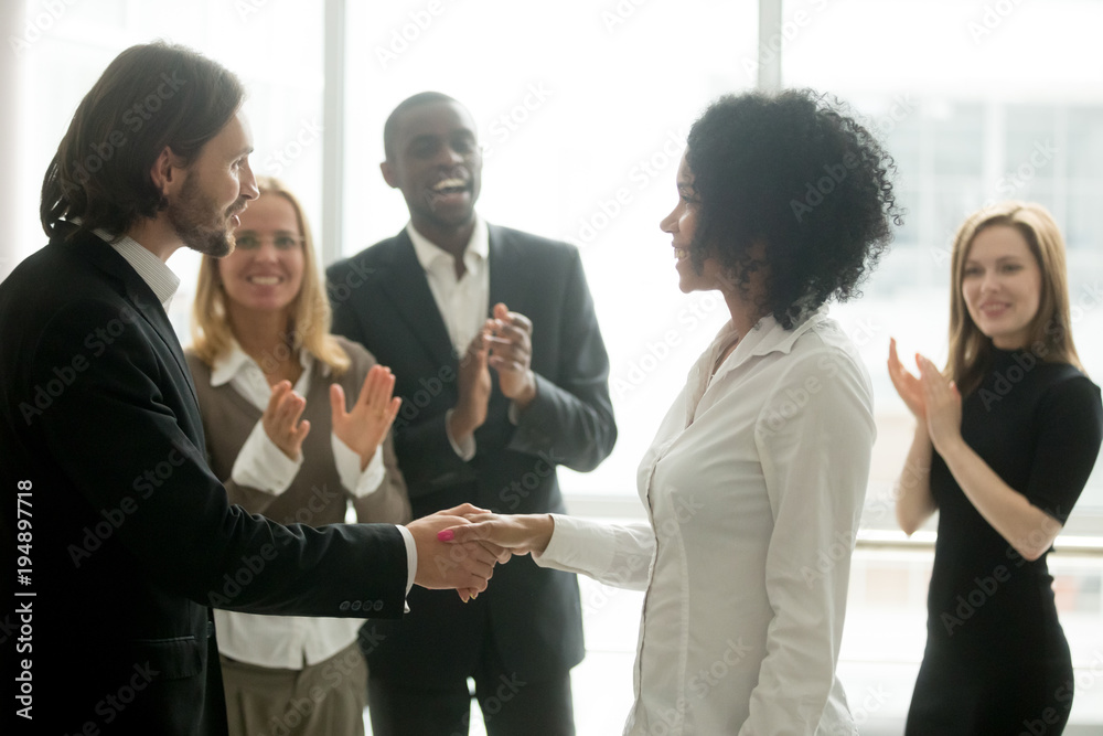 Fototapeta Grateful boss handshaking promoting african businesswoman congratulating with career achievement while colleagues applauding cheering successful worker, appreciation handshake, employee recognition