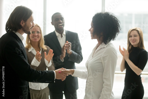 Grateful boss handshaking promoting african businesswoman congratulating with ca Canvas Print