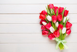 Fototapeta Tulipany - Springt time. Red tulip bouquet on the white wooden background.