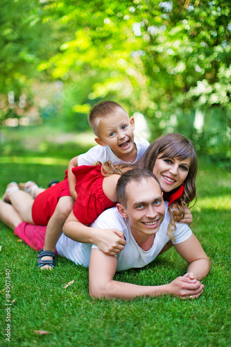 Happy family resting in the park on the lawn Wallpaper Mural