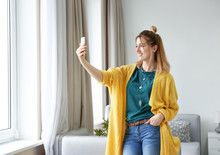 Young Woman In Yellow Cardigan Taking Selfie Indoors