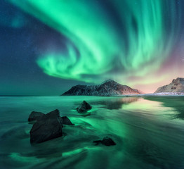 Fototapeta Niebo Aurora. Northern lights in Lofoten islands, Norway. Sky with polar lights, stars. Night winter landscape with aurora, sea with sky reflection, stones, sandy beach and mountains. Green aurora borealis