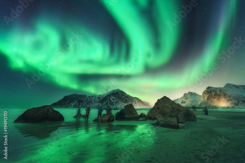 Poster Aurore polaire Green aurora borealis and photographers. Aurora. Northern lights in Lofoten islands, Norway. Starry sky with polar lights. Night landscape with aurora, sea, people, stones, sandy beach and mountains.
