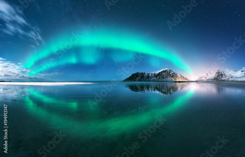 Photo sur Toile Aurore polaire Aurora. Northern lights in Lofoten islands, Norway. Starry blue sky with polar lights. Night winter landscape with aurora, sea with sky reflection, beach, mountains, city lights. Green aurora borealis