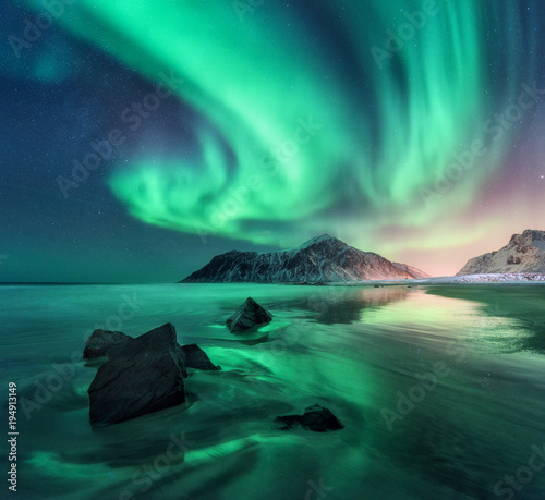 Poster Landschap Aurora. Northern lights in Lofoten islands, Norway. Sky with polar lights, stars. Night winter landscape with aurora, sea with sky reflection, stones, sandy beach and mountains. Green aurora borealis