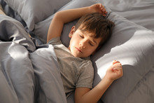 Cute Little Boy Sleeping In Bed At Home