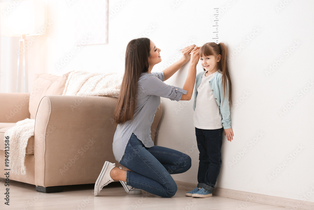 Fototapety, obrazy: Young woman measuring her daughter's height indoors