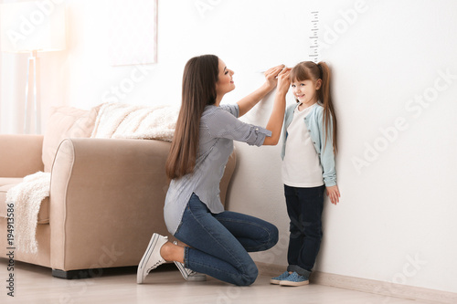 Fotografía  Young woman measuring her daughter's height indoors