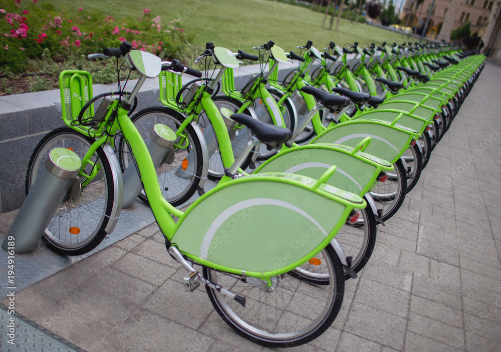Fototapeta Row of new green public sharing bicycle lined up on the street , Modern concept of ecological transportation, Bike urban transport