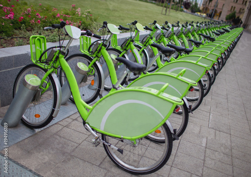 Obraz Row of new green public sharing bicycle lined up on the street , Modern concept of ecological transportation, Bike urban transport - fototapety do salonu