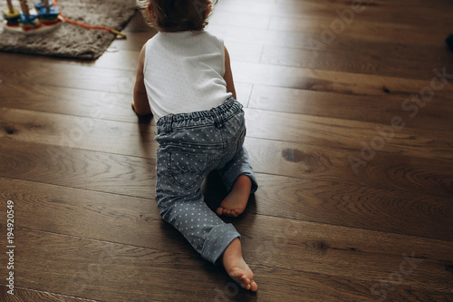 close-up of the baby's legs that creeps towards the toys on the wooden floor Canvas Print