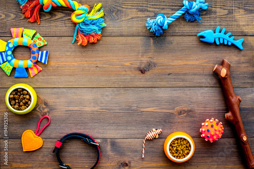 Obraz Pet accessories. Toys near bowls with animal feed, collar on dark wooden background top view copy space - fototapety do salonu