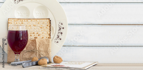 Pack of matzah or matza, Passover Haggadah, red kosher wine and white passover seder plate on a vintage wood background. Jewish Passover holiday composition with copy space.