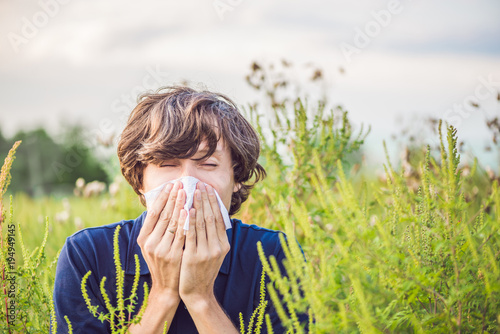 Young man sneezes because of an allergy to ragweed Canvas Print