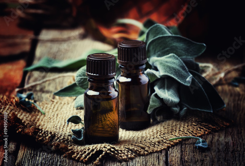 Photo  Essential sage oil in brown bottle on the vintage wooden blackground, rustic sty