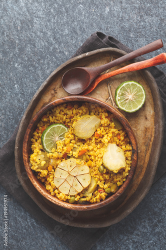 Curry bulgur with vegetables in wooden bowl. Dark background, top view, vegan meal concept.