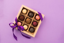 A Set Of Assorted Chocolates In A Paper Box With A Satin Purple Ribbon On A Bright Background