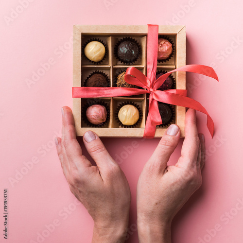 Poster Confiserie Box with chocolate sweets of different varieties in female hands. The box is decorated with a pink satin ribbon and bow.