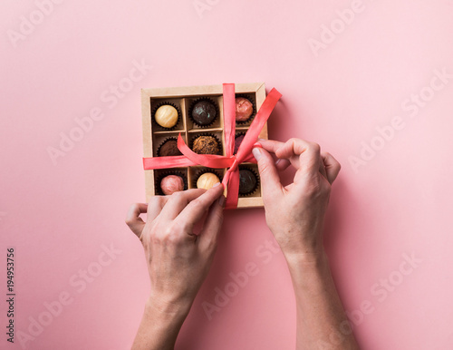 Foto auf Leinwand Süßigkeiten Female hands tie a bow from a satin ribbon on a box with a set of chocolates. Trendy pink background.