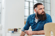 Young bearded businessman watching to the side