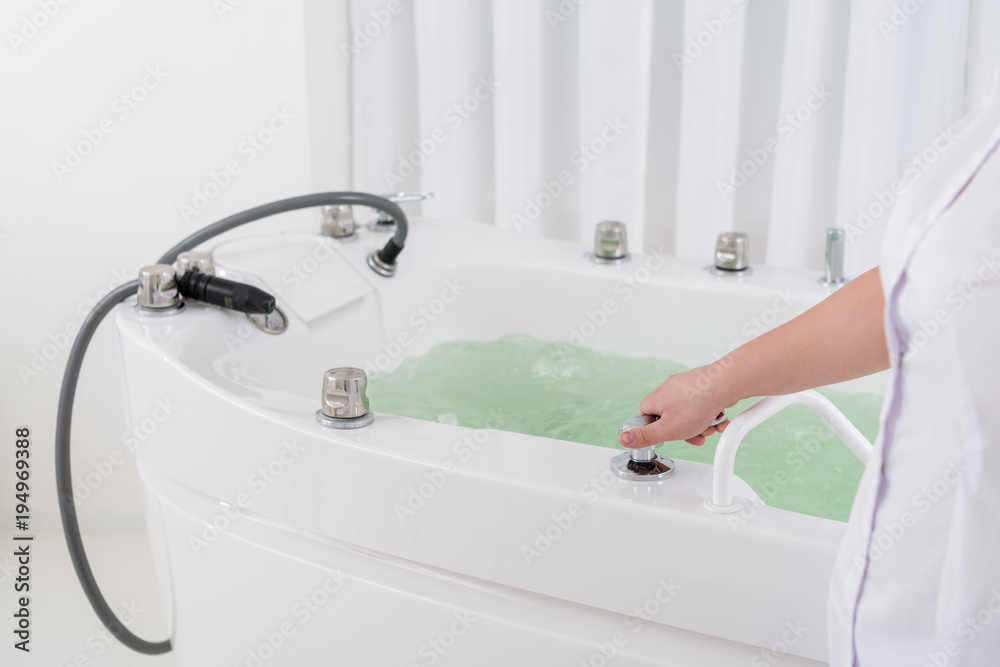 Fototapeta cropped shot of spa salon assistant regulating water in hydro bath