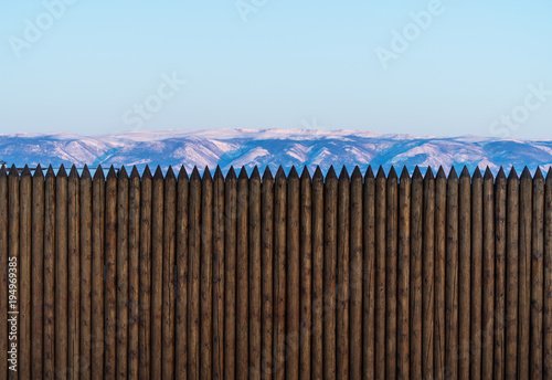 Wooden tree trunks fence wall with snow mountain and clear sky view Wallpaper Mural