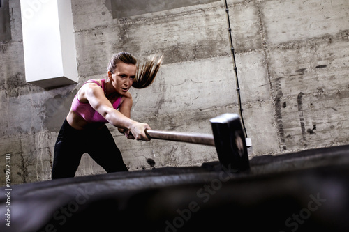 Fotomural Fitness woman hitting wheel tire with hammer sledge in the gym, cross fit training