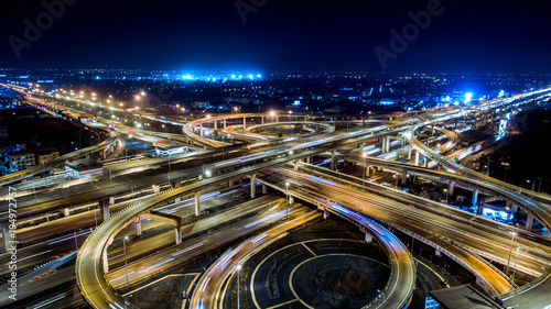 Fotobehang Nacht snelweg The highway in the big city, expressway enter the city, blue light picture by drone on top view.