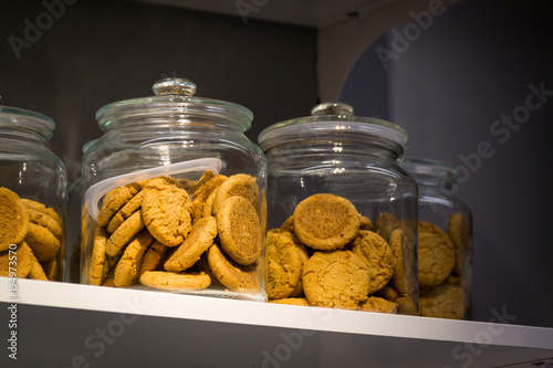 Cuadros en Lienzo Chocolate biscuits in a glass jar on a wooden shelf.