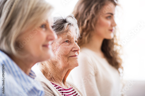 Fotografia  A teenage girl with mother and grandmother at home.