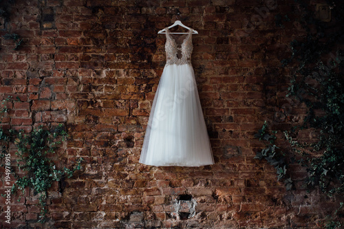 beautiful bridal wedding dress hanging on a hanger on a brick wall ...