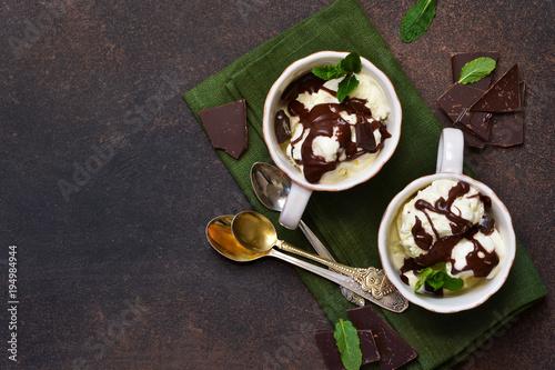 Zdjęcie XXL Lody waniliowe z kawałkami czekolady i sosem z gorącej czekolady. Letni zimny deser.