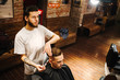 Creating new hair look. Making haircut look perfect. Young bearded man getting haircut by hairdresser while sitting in chair at barbershop