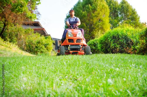 Gardener driving a riding lawn mower in garden