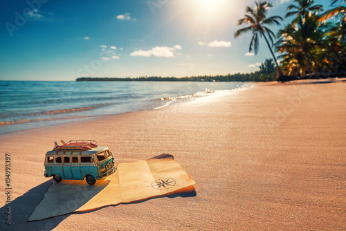 Fototapeta Vintage miniature van and old treasure map on the tropical beach at sunrise, travel concept