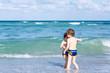 Two kid boys running on ocean beach. Little children having fun