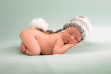 Likable And Pretty Sleeping Newborn Baby Girl With In A Knitted Hat On A Blue Background