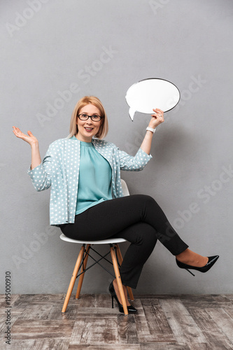 Poster  Smiling business woman holding speech bubble.